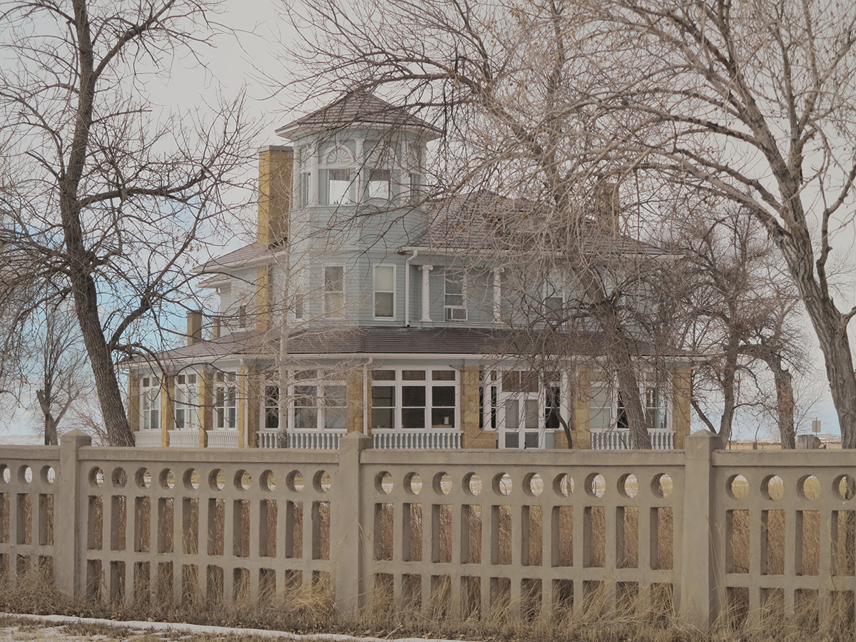 color image of a large grey and stone house in background with a fence in foreground