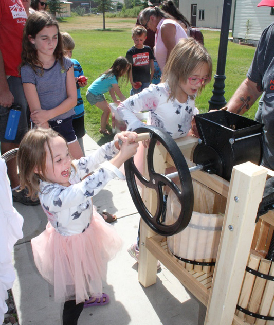 color image a little girl in a white top and pink tutu cranking the handle on a cider press with a huge smile on her face