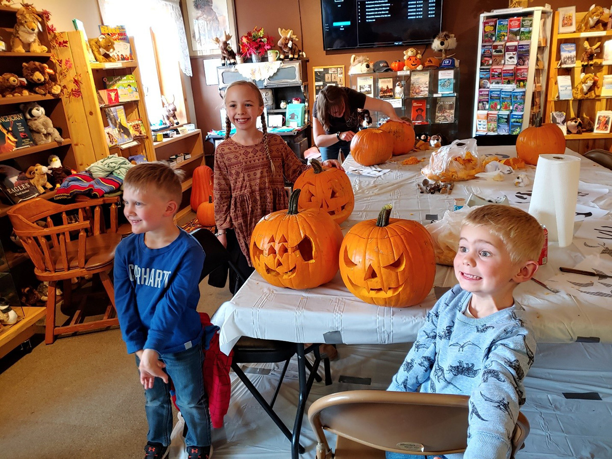 color image of 2 boys and girl standing beside the jack-o-lannterns that they carved