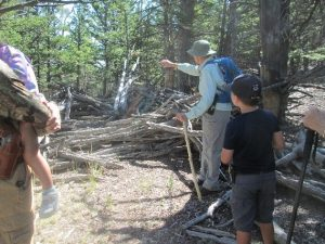 color photo of a small group of people looking at a small lodge pole pine structure known at a sheep trap
