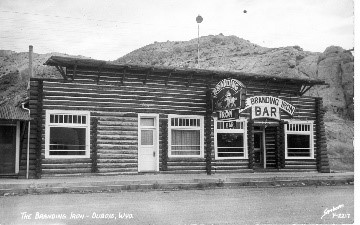 "black and white image of a small log building with a sign above the door that reads, ""BAR"""