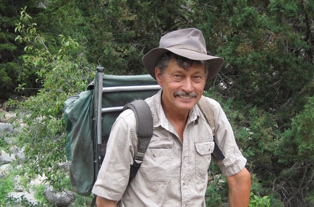 color image of a man in a tan shirt and hat wearing a green backpack standing in a forest