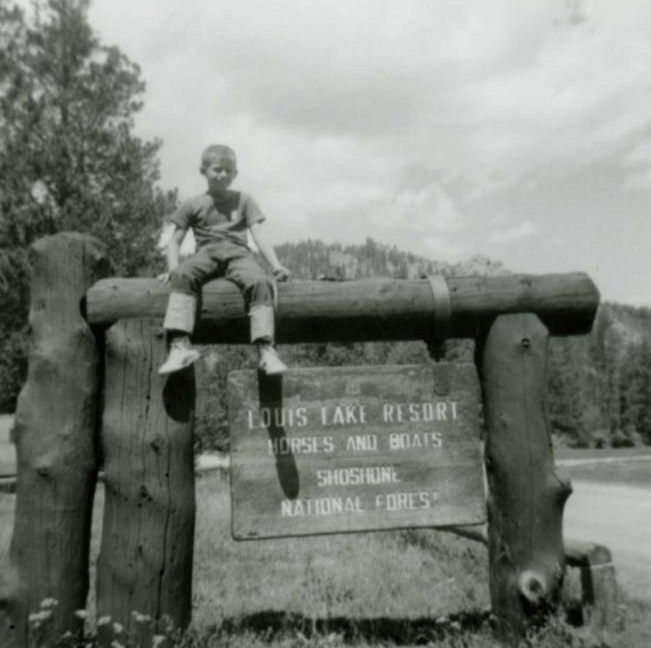 historic black and white image of a young boy sitting on top a large log structure with a sign hanging between the timbers