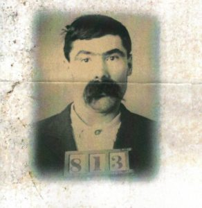 sepiatone image of a man with a number on his chest (like a mugshot)