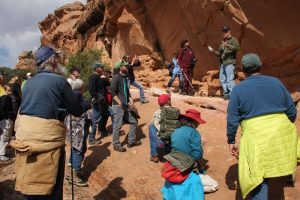 image of a group of people looking at petroglyphs on a red rock wall